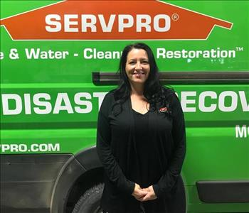 A female standing in front of a SERVPRO truck