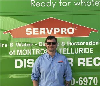 male employee Posing in front of the SERVPRO truck