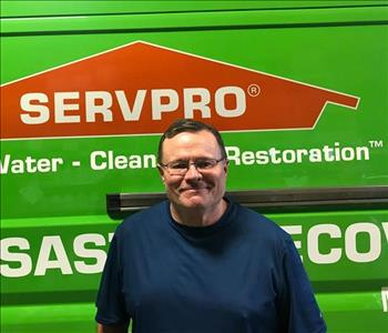 A man standing in front of a SERVPRO vehicle.