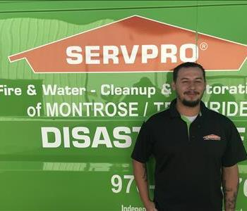Male employee Standing with a SERVPRO  truck background