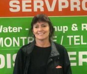 female employee standing in front of a SERVPRO truck