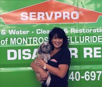 Female office employee holding a dog in front of a SERVPRO vehicle.