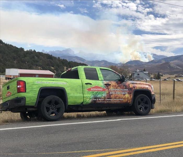 SERVPRO vehicle parked on side of country road with a house and further in the background smoke raining up from the hills and