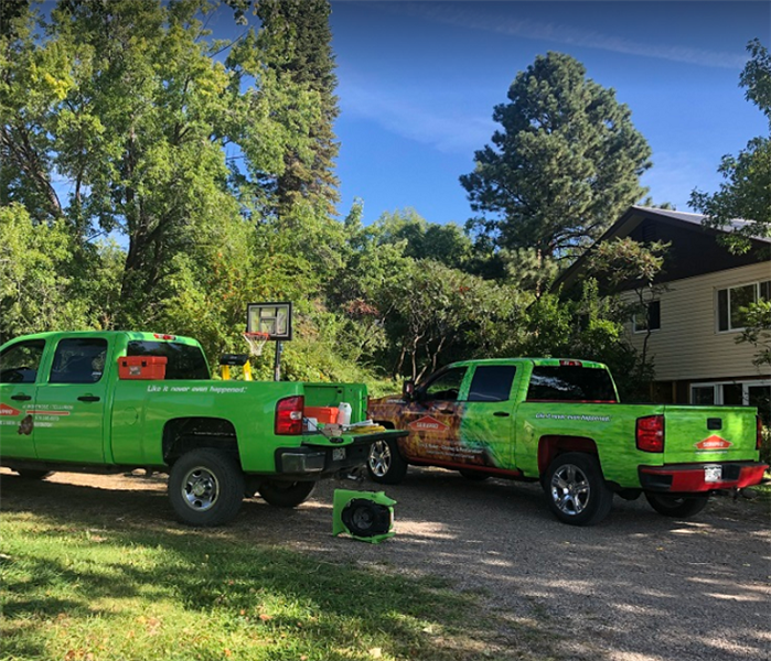 Two SERVPRO trucks and drying equipment in front of house