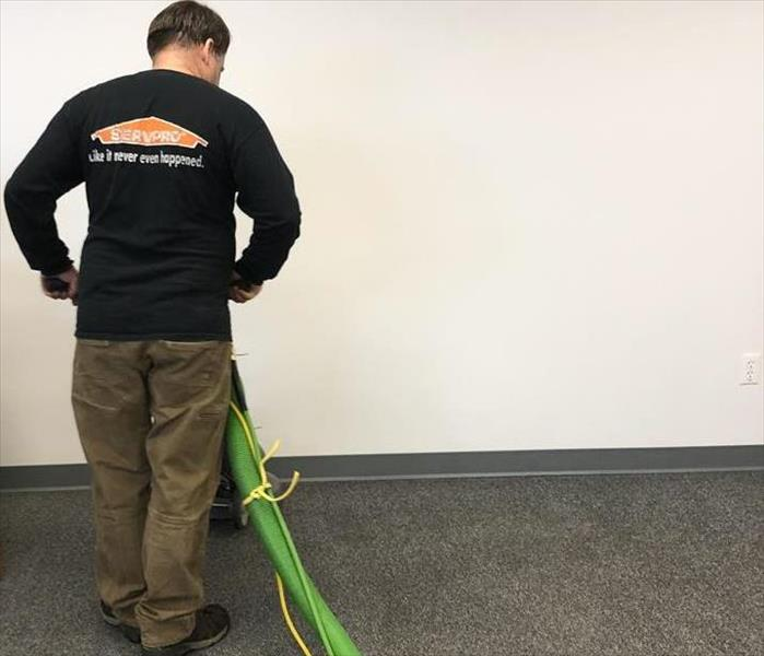SERVPRO employee running a commercial shop vacuum on carpet flooring.