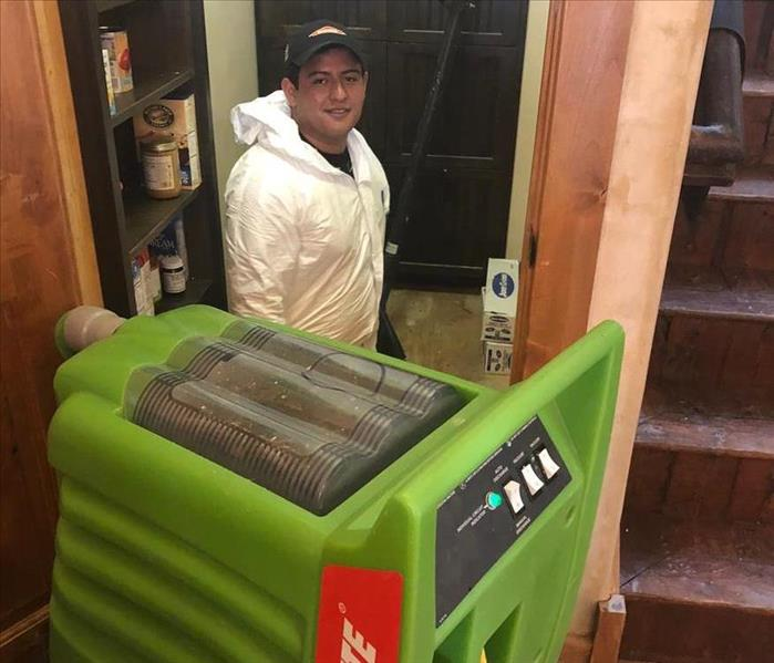 A SERVPRO employee standing in a home with equipment.