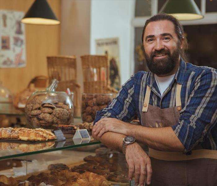 A man with a brown apron on in a bakery.